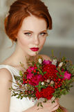 Very pretty sophisticated red-haired girl with a bouquet in hand. In the interiors of the studio, close-up Stock Photography