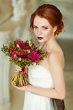 Very pretty sophisticated red-haired girl with a bouquet in hand Stock Photography