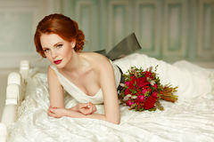 Very pretty sophisticated red-haired girl with a bouquet in his. Hand lying on the bed, in the interiors of the studio Stock Photo