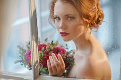 Very pretty sophisticated red-haired girl with a bouquet in his. Hand standing outside the window that displays the raindrops, close-up Royalty Free Stock Photos