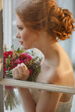 Very pretty sophisticated red-haired girl with a bouquet in his. Hand standing outside the window and looks off into the distance at which visible raindrops Stock Photos