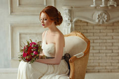 Very pretty sophisticated red-haired girl sitting in a chair wit. H a bouquet in hand, in the interiors of the studio Royalty Free Stock Photography
