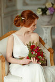 Very pretty sophisticated red-haired girl sitting in a chair wit. H a bouquet in hand, in the interiors of the studio Stock Photos