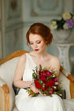 Very pretty sophisticated red-haired girl sitting in a chair wit. H a bouquet in hand, in the interiors of the studio Stock Photography