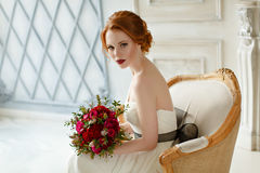 Very pretty sophisticated red-haired girl sitting in a chair wit. H a bouquet in hand, in the interiors of the studio Royalty Free Stock Photos