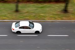 Very quickly driving white sports German coupe on a city street royalty free stock image