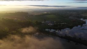 Aerial view of a farm during a foggy sunrise. A very rainy week created the perfect sunrise over a lake in the morning! Great views of farmland and fog stock footage