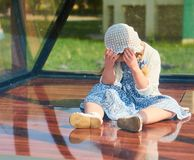 Very realistic doll resembling a crying little girl sitting behind glass royalty free stock photos