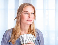 Very rich girl. Closeup portrait of attractive serious young business woman holding in hands american dollars, winning financial lottery, success concept Royalty Free Stock Photos