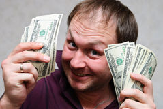 The very rich man smiles. The rich man smiles and shows off bundles of hundred-dollar bills. Focus on dollars, not face royalty free stock images