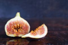 A very ripe blue fig on a dark background. Organic fruits. Healthy food stock image