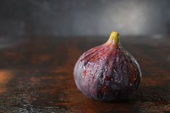 A very ripe blue fig on a dark background. Organic fruits. Healthy food stock photography