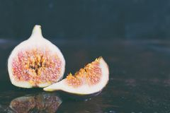 A very ripe blue fig on a dark background. Organic fruits. Healthy food royalty free stock image