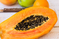Very ripe juicy papaya cut in half on wood kitchen table with citrus fruits, apples, knife Stock Photography