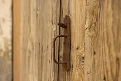 Old brown barn handle. Very rusty old barn handle on a old wooden door royalty free stock images
