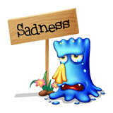 A very sad blue monster crying near a wooden signage Stock Photo