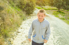 Sad boy crying. Sad young boy crying while walking up the country road Stock Photo