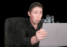 Very sad at broken computer. Very unhappy guy looking at his smoking broken computer sad expression Stock Images