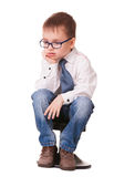Very sad clever kid on white. Very sad clever kid in jeans and shirt sitting on small chair isolated on white background Stock Image
