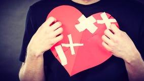 Very sad man holding broken heart Stock Photography