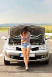 Very sad woman in front of broken car Stock Photography
