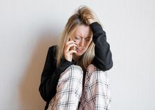 Very sad woman talking on phone. Depressed woman sitting on the floor Royalty Free Stock Photo