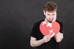 Very sad young man holding broken heart Royalty Free Stock Photo