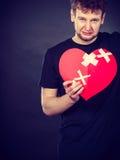Very sad young man holding broken heart Stock Photo