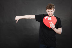 Very sad young man holding broken heart Royalty Free Stock Images