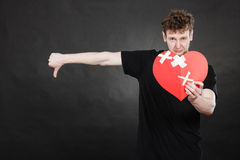 Very sad young man holding broken heart Stock Photography