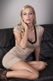 Very sensual blonde sitting on a black sofa Royalty Free Stock Image