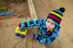 Very serious child playing with toys in the sandbox royalty free stock photos