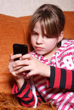 A very serious girl playing games on phone Stock Photo