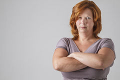 Very serious man. Woman in her forties with her arms cross and a serious look Stock Photo