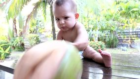 A very serious one-year-old baby throws fresh green coconut from the table. A face is carved on a coconut like a Halloween pumpkin. The concept of the end of stock video footage