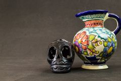 A very serious Talavera vase with a black Oaxaca skull. On a textured black background royalty free stock images