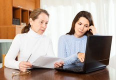 Very serious  woman and young girl at table Royalty Free Stock Photography