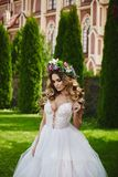 Very and hot blonde model girl, in white dress and floral wreath on her head, is walking in front of church stock image