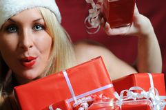 A very sexy Mrs. Santa Clause. Winter portrait of a sexy blond woman with white fur and a lot of gifts Stock Images