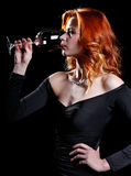 Woman with beautiful red hair is drinking a glass of red wine Royalty Free Stock Images