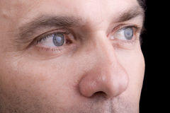 Very sharp closeup of man's face with blue eyes. Black background Royalty Free Stock Photos