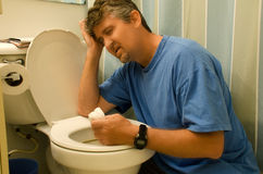 Very sick man throwing up at the toilet. An extremely ill man that has been throwing up in his toilet is leaning on the toilet seat trying to gain his composure Stock Photo