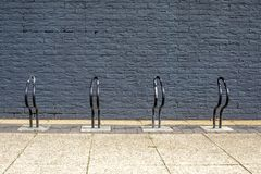 Very simple bike, bicycle racks, painted black in front of a bla royalty free stock photo