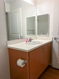 Simple bathroom vanity with mirrors and sink. A very simple portion of a residential bathroom with wood vanity, toilet paper, sink, hand soap, mirrors, and royalty free stock images