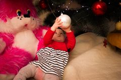 A very small girl sits under a Christmas tree with colorful decorations. New Year and Christmas tree. Small girl sits with Christmas tree. Colored lights and Royalty Free Stock Photos