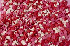 Very small heart-shaped candies are scattered across the background. Many small bright hearts in bulk stock image