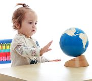 Very small but serious little girl spinning globe. Hand.Isolated on white background, Lotus Children's Center Stock Photos