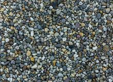 Very small and tiny pebble stone rocks in macro close up in diverse colors garden ground decoration background. Some very small and tiny pebble stone rocks in stock image