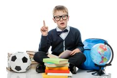 very smart boy with books, globe and soccer ball Royalty Free Stock Photos