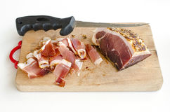 Very spicy prosciutto 1. Homemade spicy proscuitto, smoked and dried in the wind for a long time, on wooden chopping board with long, thin knife Stock Photo